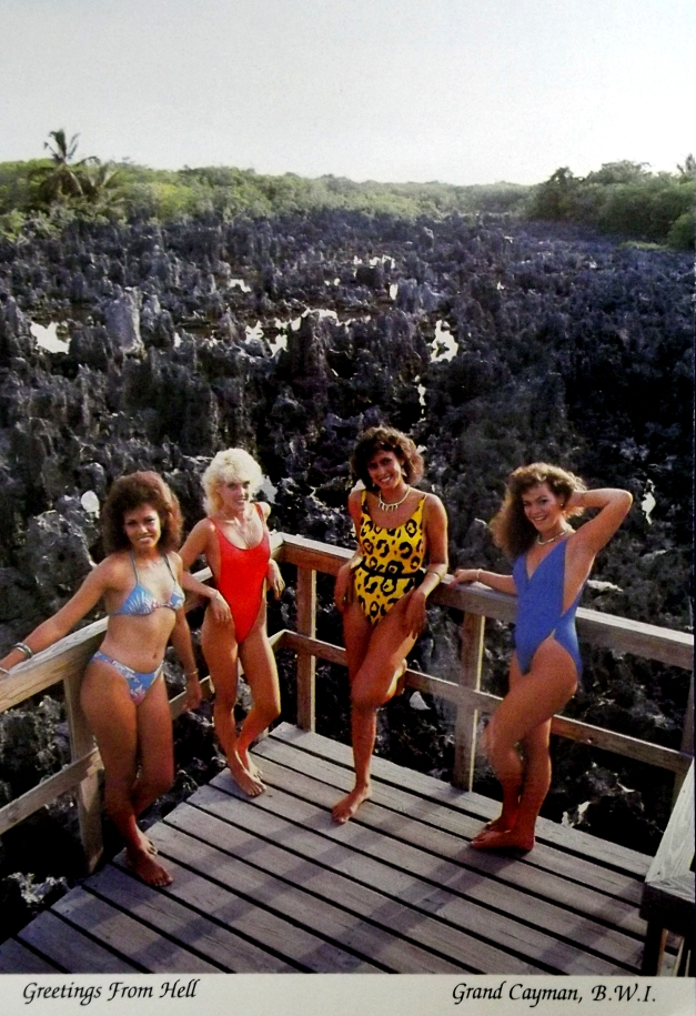 4 women in swim suits stand in front of a rocky landscape