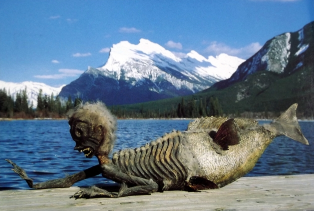 A skeleton of a mermaid type creature in front of mountain scenery