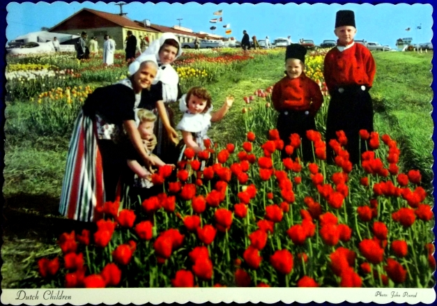 Dutch-dressed children stand in front of tulips