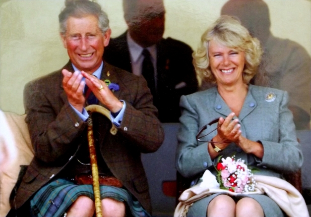 Prince Charles sits on a chair wearing a kilt