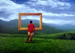 A man stands in front of a mountain gazing through a picture frame suspended in the air