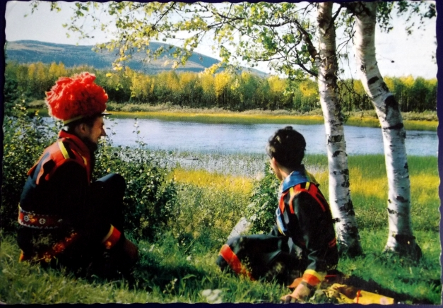 A man in a woman in traditional Swedish attire sit by a lake