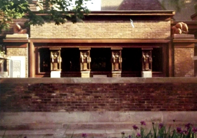 Photograph of an old brick house's porch with columns adorned with cranes