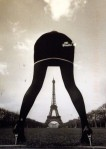 A woman straddles the Eiffel Tower