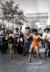 Old image of women hula hooping on the streets of Paris while cowboy musicians and a crowd look on