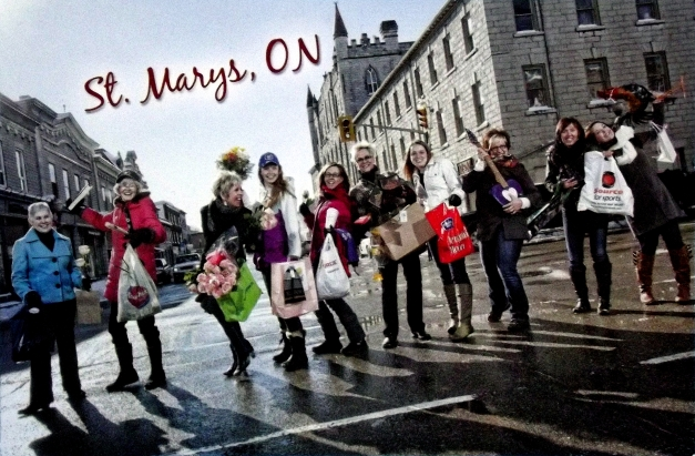 "A bunch of women stand in the street proudly showing off their purchases with the caption ""St Marys Ontario"""