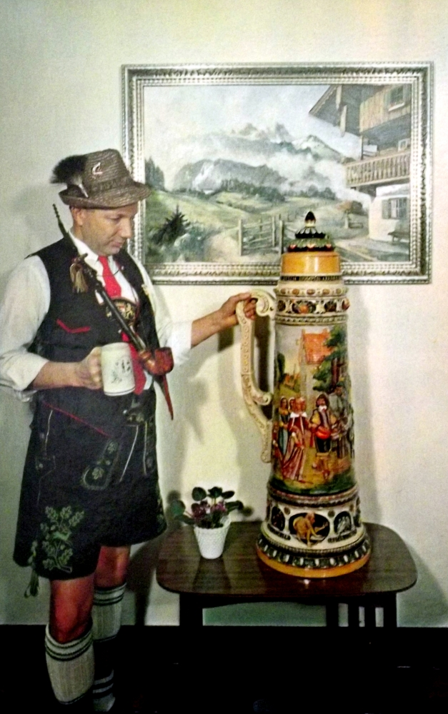 A German man dressed in lederhosen  looks at a giant stein