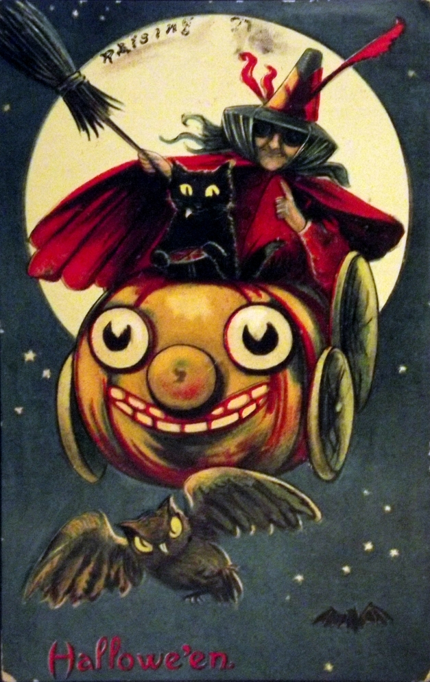 A witch and black cat ride a pumpkin car with the caption