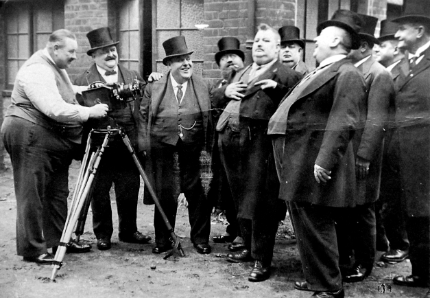 Old photo of a movie being made with various fat British men