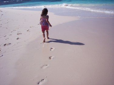 Child runs on the beach leaving footprints