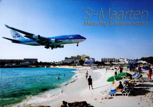 An airplane lands very close to a beach
