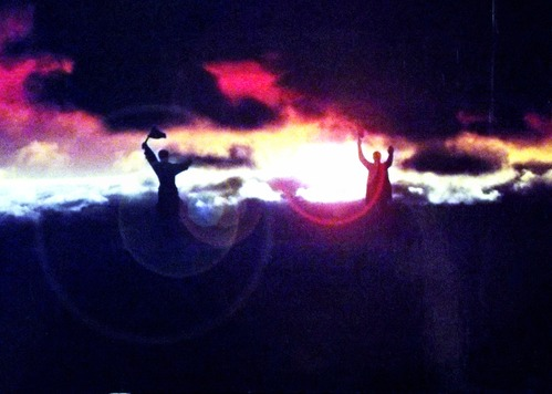 Two statues of communist figures are silhouetted by a sunset
