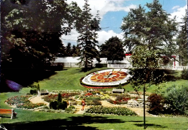 A garden on a hillside with a large floral clock