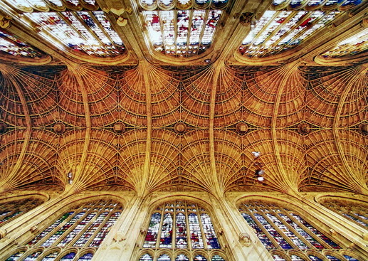 A vaulted ceiling with stained glass windows on the side