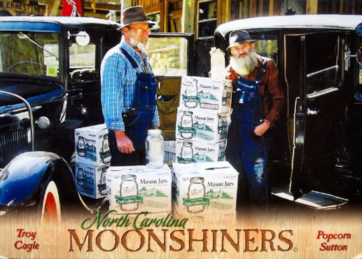 Two old men stand beside boxes of moonshine