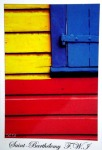 Detail of a wooden house with the boards painted yellow, blue and red