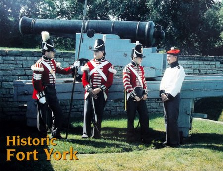 Soldiers in old British uniforms in front of a canon