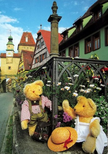 Two teddy bears in front of a medieval German town