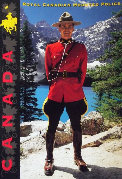A mountie in full red uniform poses before a mountain and lake