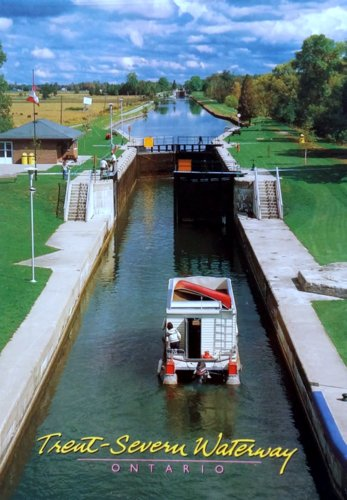 A small boat in a canal approaching a lock
