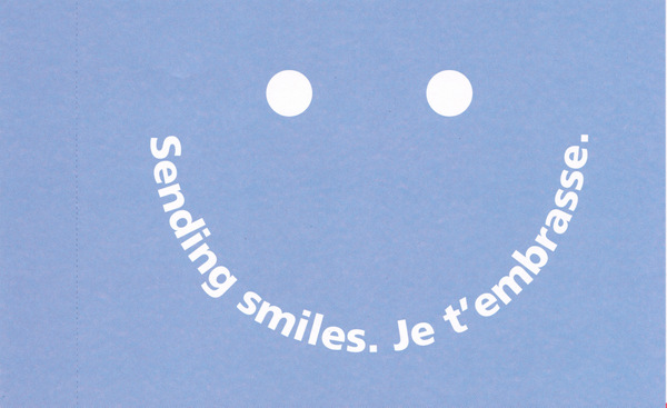 A smiley face is comprised of two dots for eyes and the expression Sending smiles and the French equivalent.