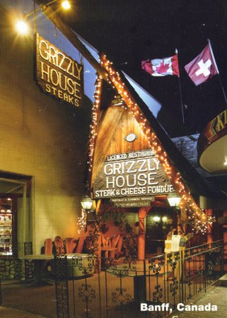 """An A-frame building is pictured with a sign that says """"Grizzly House Steak and Cheese Fondue. Banff, Canada"""""""