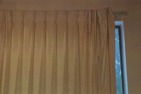 A beige curtain is pulled over a window with a small portion of the window appearing