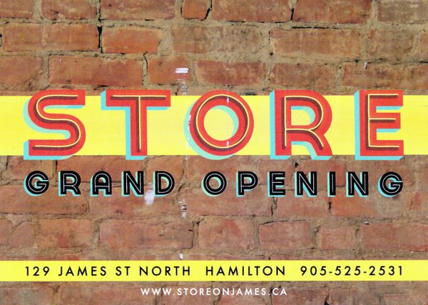 Front of postcard. It has a brick wall with the words Store Grand Opening on it