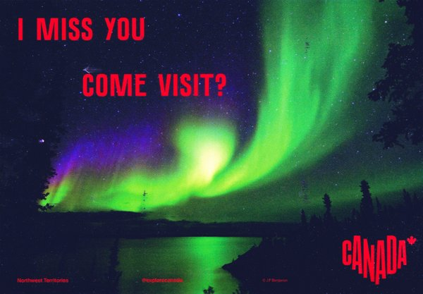 The northern lights, mostly bright green, shine over a lake. The caption says Northwest Territories Canada.