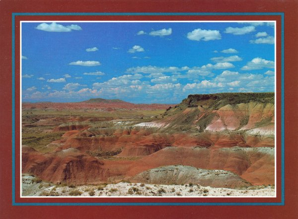 Image of a desert landscape with cliffs and buttes of various shades of brown, beige, and red